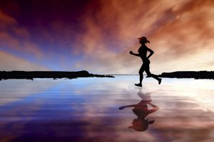runner on beach at sunset