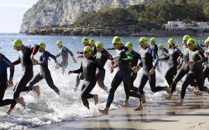 men running into ocean